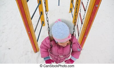 little girl teetering in deep snow city playground, winter