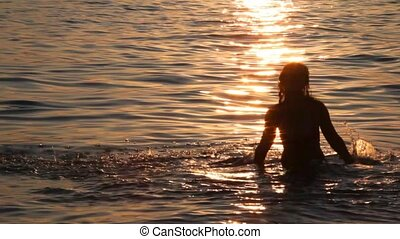 silhouette of young woman splashing water in sea with sunset...