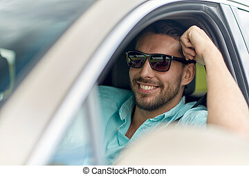 happy smiling man in sunglasses driving car - road trip,...