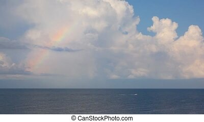 cutter moving on sea under sky with clouds and rainbow