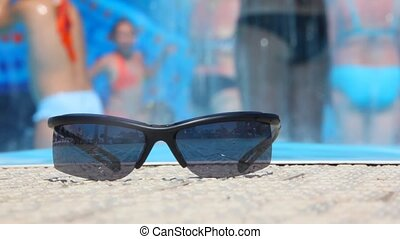 summer background, people in water park, focus on sunglasses