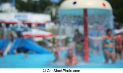 summer defocused background, people in water park, boy walks...