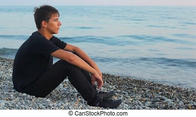 teenager sits on pebble beach and looks at sea, profile