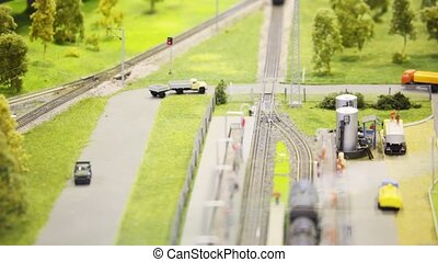 train pushes tank on rail in modern toy city to fuel station among roads with small cars and trees