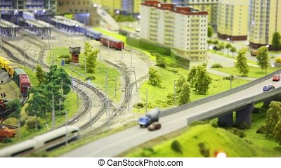 in modern toy city train goes by rail to trainpark among houses and trees