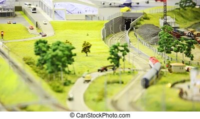 toy passenger train with two wagon drives to tunnel on rail in toy modern sity near airport