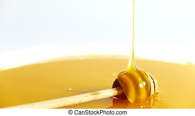 honey dripping in a bowl full