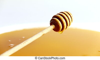 honey dripping in a bowl full of honey, vintage look.