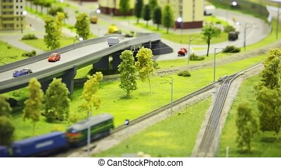 toy train bring cargo wagon on rail in modern toy city among highway, house and trees