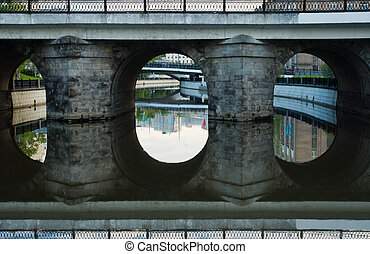 stone bridge with reflection in water