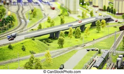 toy train pushes empty cargo wagon on rail in modern toy...