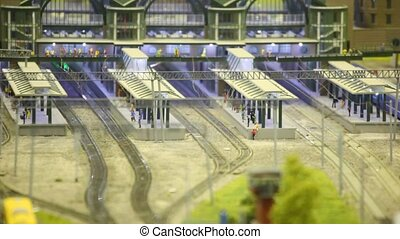 in modern toy city passenger train goes by rail to platform in station