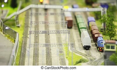 locomotive pushes tank on rail in modern toy city through...