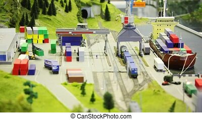 in modern toy sity train bring tank-wagon to loader in port near transport ship