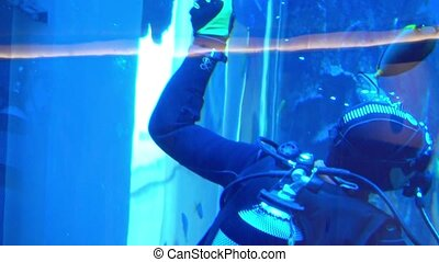Scuba diver washing big water tank glass from inside....