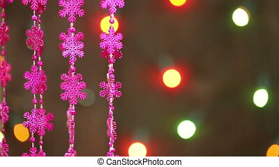 Garland of pink snowflakes on a background of a garland...