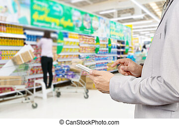 Hand of Businessman use Mobile Tablet in supermarket - Hand...