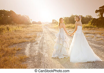 Bride and Bridesmaid on a Country Road - Attractive young...