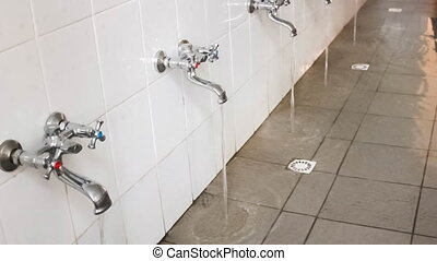 rows of steel taps in the bathroom, looped, loopable, motion...