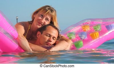 man and woman embracing on inflatable mattress in swimming pool