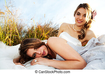 Bride And Bridesmaid Lying in the Grass