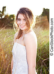 Attractive Young Woman Standing in the Grass - An attractive...
