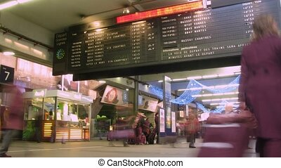 Board with departure of trains, passengers in a station...