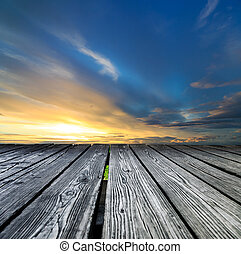 Rostrum made of wooden planks on sunset background