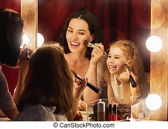 Mother and daughter are doing makeup - Happy loving family....