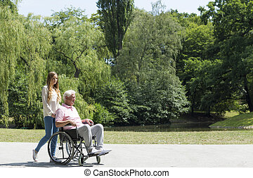 Getting out in the fresh air - Elderly man on a wheelchair...