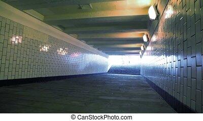 family of three running in underground passage to camera,...