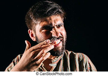 Drugged man with cocaine dust on teeth on black background