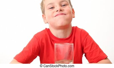 small boy takes glass, drinks water from it and smiles