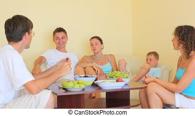 people sitting at table, eating fruits and talking indoor