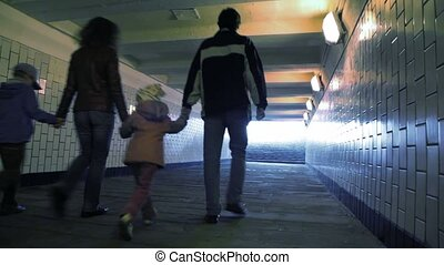 family of four walking in underground passage from camera,...