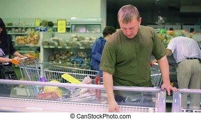 man buying food stuff in supermarket