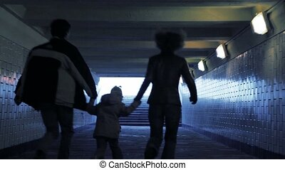 family of three persons running in underground passage from...