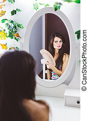 Beautiful woman looking into the mirror