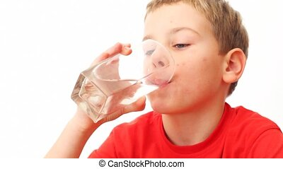 boy takes glass, drinks all water in it and look. Lapse time
