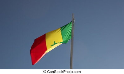 Textile flag of Senegal on a flagpole in front of blue sky