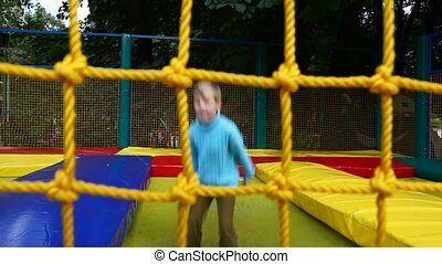 young happy boy jumping on inflatable trampoline in amusement park behind net