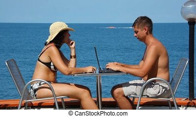 man using notebook and woman in swimsuit with cell phone sits at table
