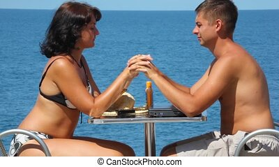 man and woman sits at table with join hands kissing, sea in...