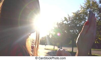 Beautiful brunette girl making selfie in the park, warm...