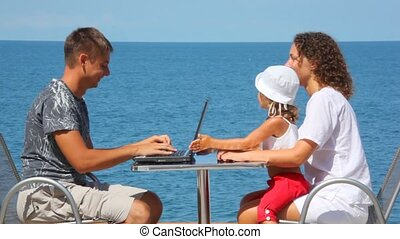 smiling family of three persons with notebook sits at table, sea in background