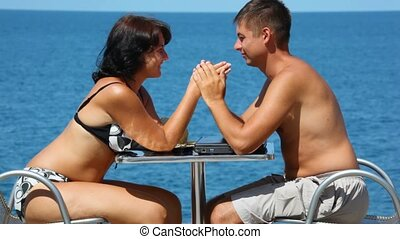 man and woman in swimsuit sits at table, join hands, sea in background