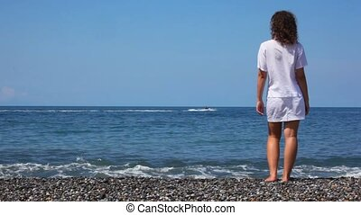 standing young woman on rocky beach looks at cutter in sea