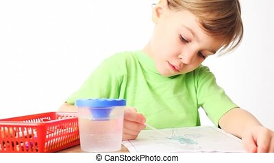 girl sits at table and paints by water picture on white background