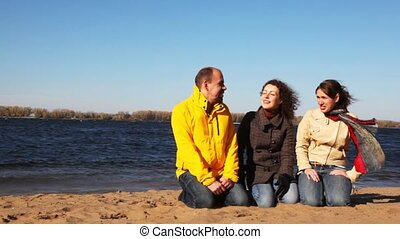 man and two woman sits on sand of river and talk with each other