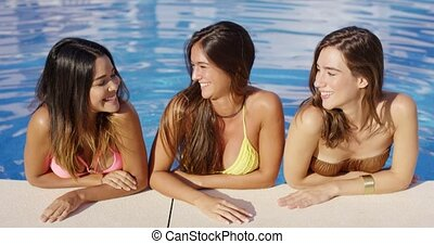 Three happy young women relaxing in a pool